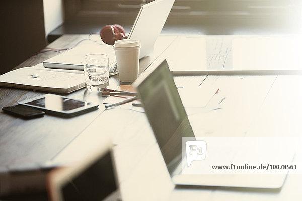 Laptops  digitales Tablett und Papierkram auf dem Tisch im sonnigen Büro