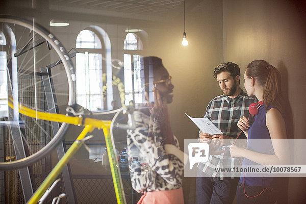 Gelegentliche Geschäftsleute diskutieren Papierkram im Büro