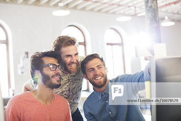 Lächelnde Gelegenheitsunternehmer  die am Computer im Büro arbeiten