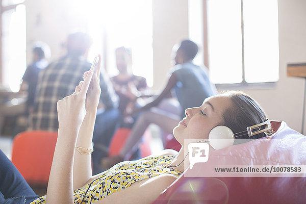 Lässige Geschäftsfrau beim Entspannen mit Kopfhörer und digitalem Tablett auf Bohnensäckchenstuhl