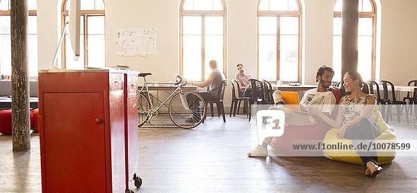 Lässige Geschäftsleute arbeiten am Laptop auf Sitzkissenstühlen im Großraumbüro