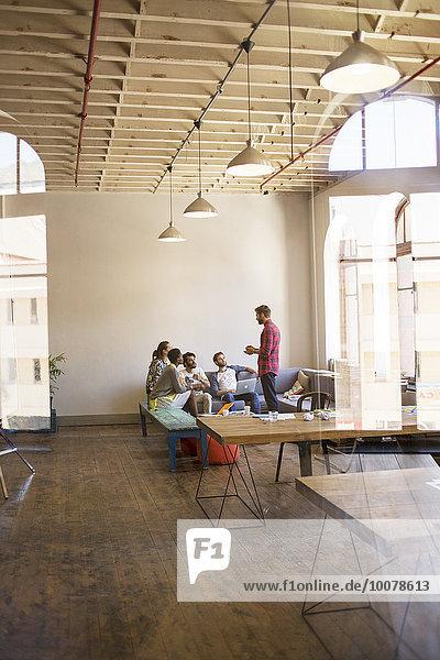 Kreativer Geschäftsmann leitet Meeting im offenen Büro