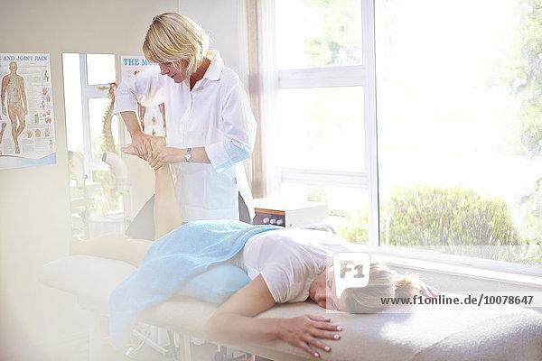 Physiotherapeutin massiert den Fuß der Frau