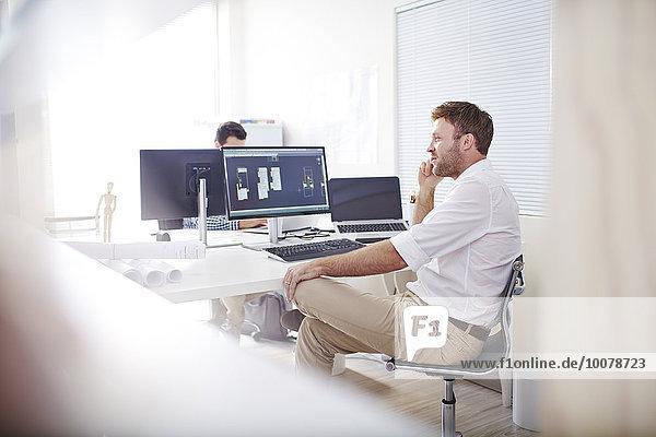 Architekt im Gespräch mit dem Handy am Computer im Büro