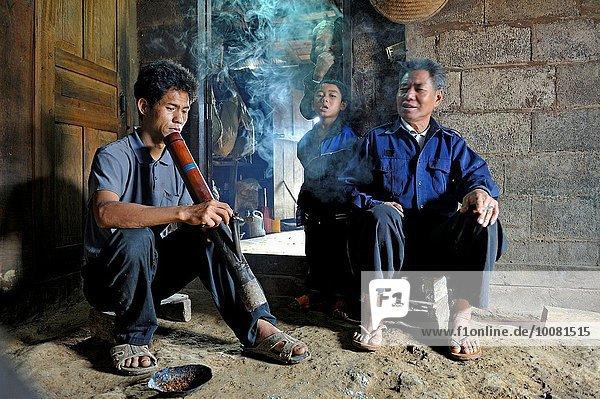 rauchen rauchend raucht qualm qualmend qualmt Berg Mann Dorf Tabak umgeben Bambus Südostasien Laos Volksstamm Stamm