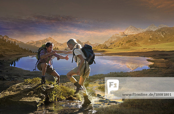 Caucasian hikers walking near remote lake  Lai da Vons  Canton Graubunden  Switzerland