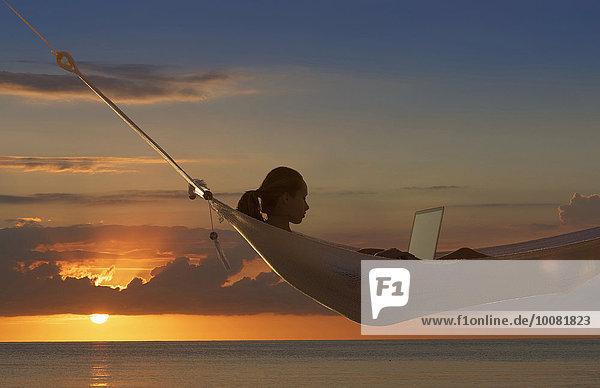 nahe benutzen Europäer Frau Notebook Sonnenuntergang Ozean Hängematte