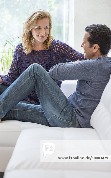 Couple talking on living room sofa