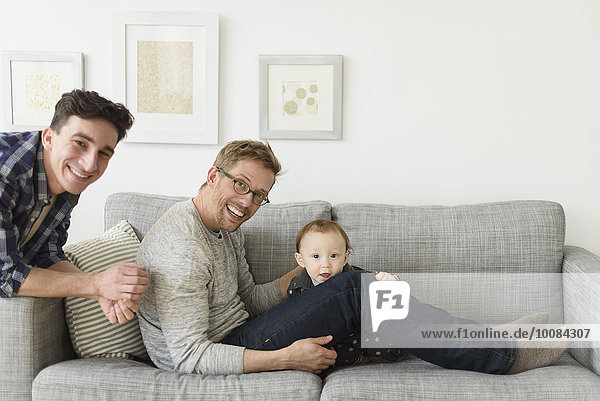 Caucasian gay fathers and baby relaxing on sofa