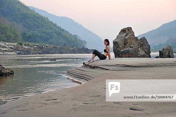sitzend Sandbank Frau Fluss Südostasien