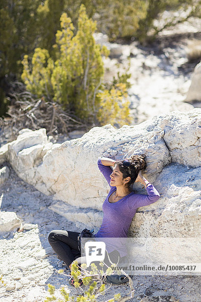 Hispanic woman relaxing on rocky hillside