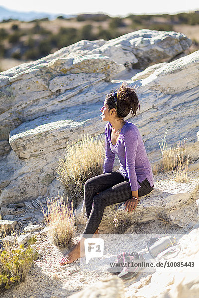 Hispanic woman sitting on rocky hilltop