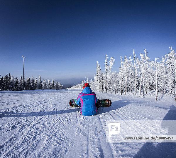 sitzend Europäer Snowboardfahrer Schnee Hang