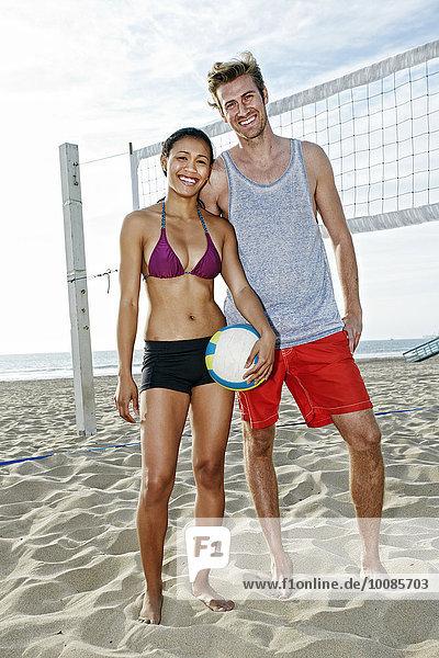 Friends smiling near volleyball net on beach