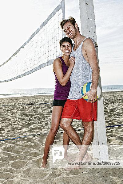Couple hugging near volleyball net on beach