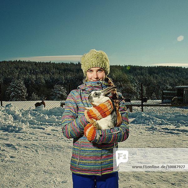 Caucasian girl hugging rabbit in snowy field