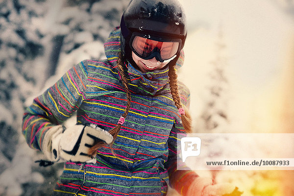 Caucasian girl wearing helmet and goggles in winter