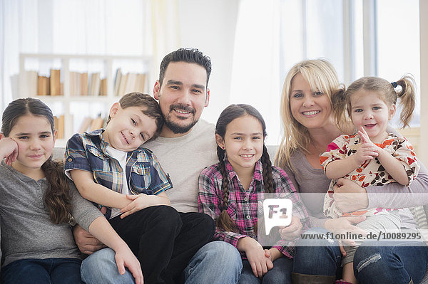 Caucasian parents and children smiling in living room