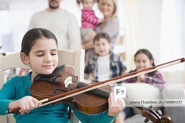 Caucasian girl playing violin in living room