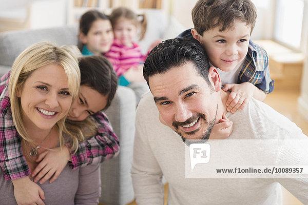 Caucasian parents carrying children piggyback in living room