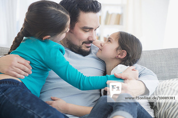 Caucasian father and daughters hugging on sofa
