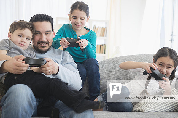 Caucasian father and children playing video games on sofa