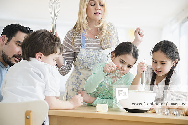 Caucasian parents and children baking in kitchen