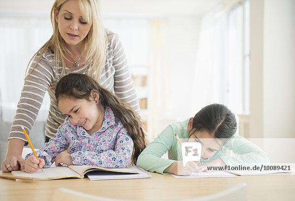 Caucasian mother helping daughters do homework