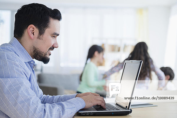 Caucasian man using laptop at desk