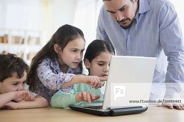 Caucasian father and children using laptop