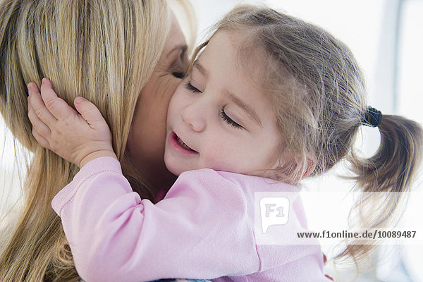 Close up of Caucasian mother kissing daughter