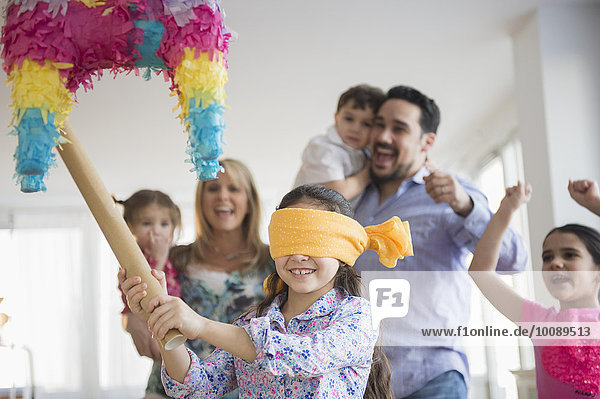 Caucasian girl hitting pinata at birthday party