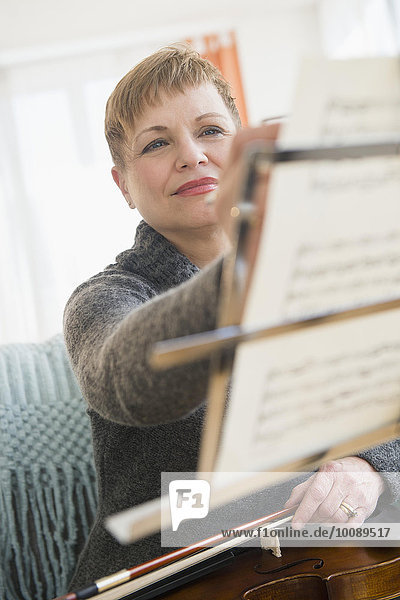 Caucasian violinist writing on sheet music