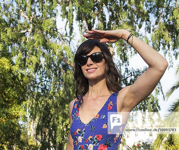 Hispanic woman shielding her eyes from sun