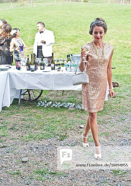 Portrait of wedding guest holding drink  smiling
