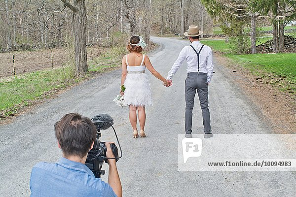 Bride and groom on country road  holding hands  rear view  videographer in shot