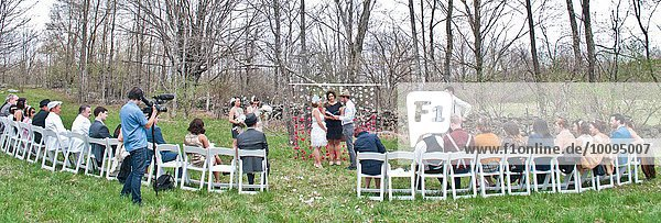 Bride and groom  during ceremony  with guests sitting around  panoramic view