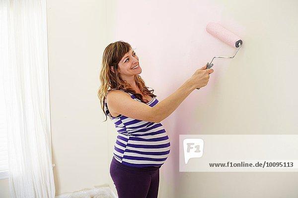 Schwangere Frau malt Kinderzimmerwände rosa