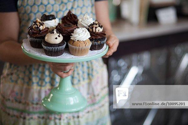 Bäckereibesitzer trägt Tablett mit allergikerfreundlichen Muffins Bäckereibesitzer trägt Tablett mit allergikerfreundlichen Muffins