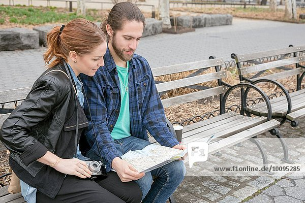 Couple map-reading on park bench  New York  New York  USA