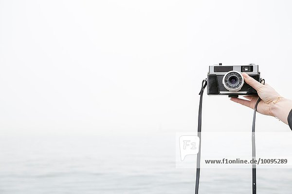Person taking selfie with camera  sea in background