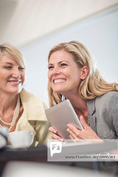 Geschäftsfrau mit digitalem Tablett beim Geschäftsessen