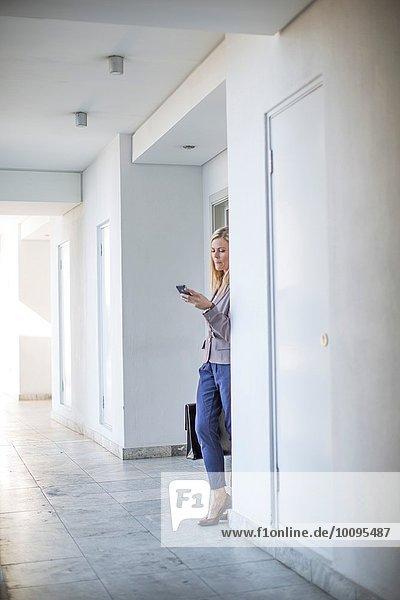 Mittlere erwachsene Geschäftsfrau liest Smartphone-Text im Hotelkorridor