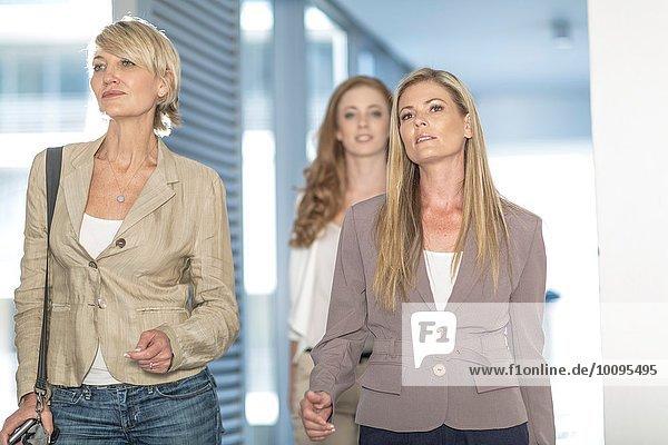 Drei entschlossene Geschäftsfrauen gehen im Hotelgang spazieren