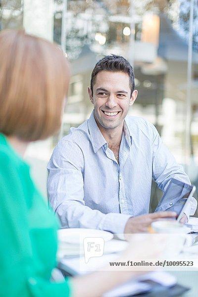 Treffen von Geschäftsfrau und Mann bei einer Kaffeepause auf der Hotelterrasse