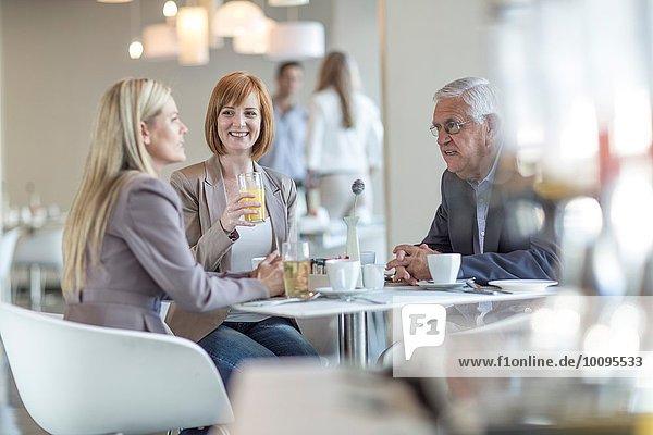 Senior Geschäftsmann im Gespräch mit dem Team am Frühstückstisch im Hotelrestaurant