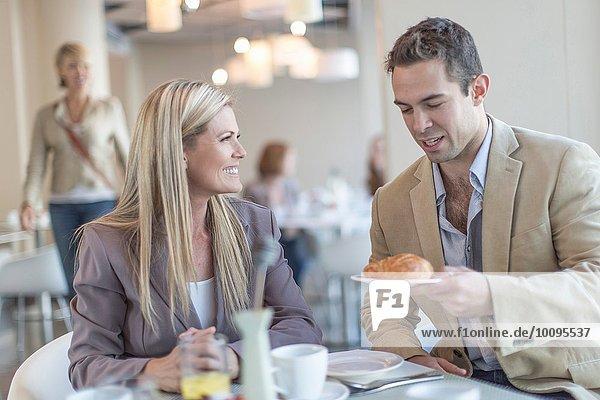 Geschäftsmann übergibt Croissant an Kollegen beim Frühstück im Hotelrestaurant