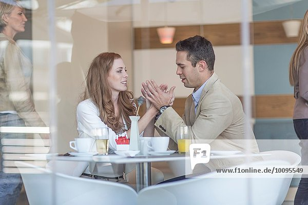 Romantisches Geschäftspaar hält Händchen am Frühstückstisch des Hotels