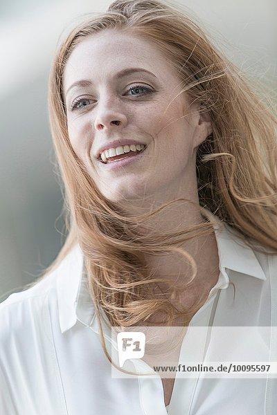 Porträt einer schönen jungen Frau mit langen roten  windgepeitschten Haaren