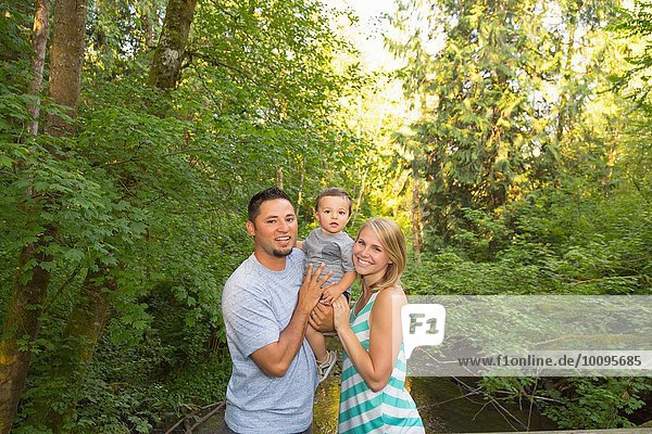 Portrait of couple with toddler son in park